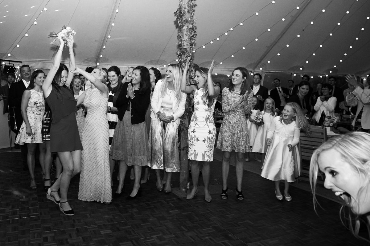 Bride throwing her bouquet flowers in Devon
