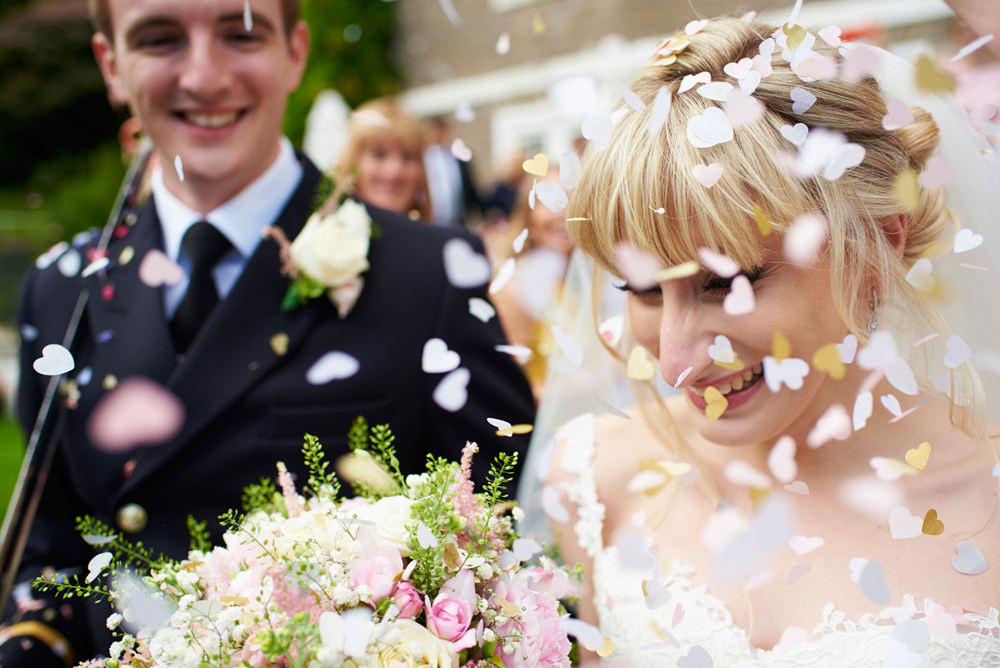 close up of bride and groom during colourful confetti shot