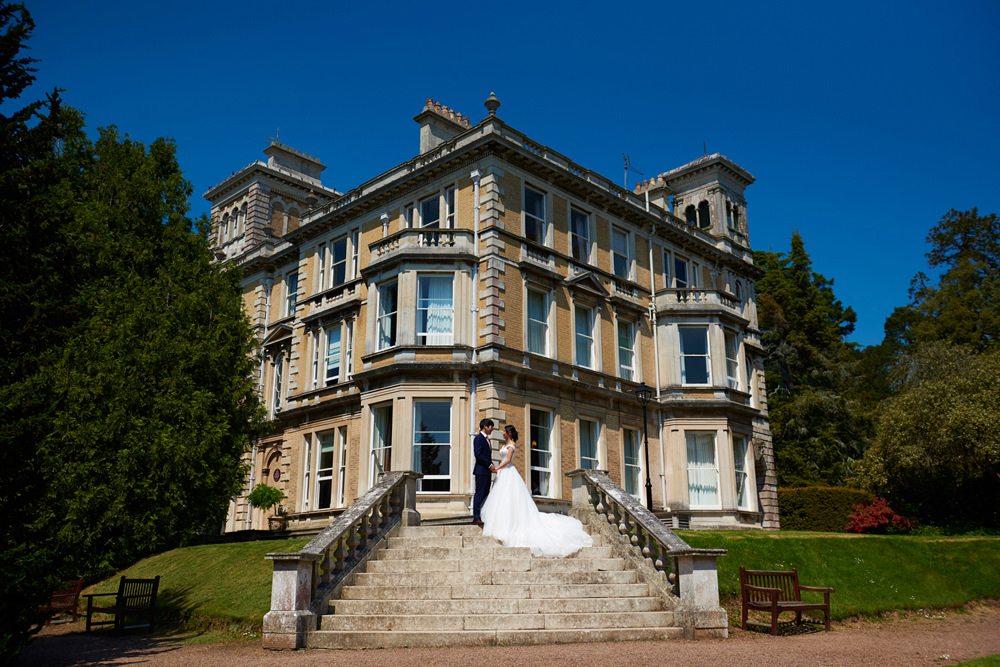 bride and groom standing on Reed Hall stairs