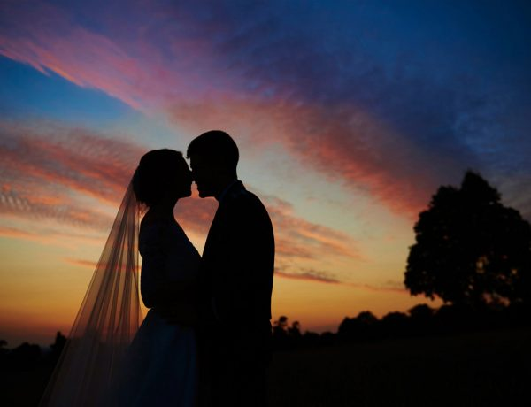 Sunset with bride and groom silhouette and beautiful sky