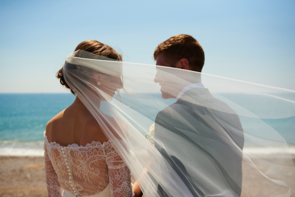 bride and groom and veil and sea