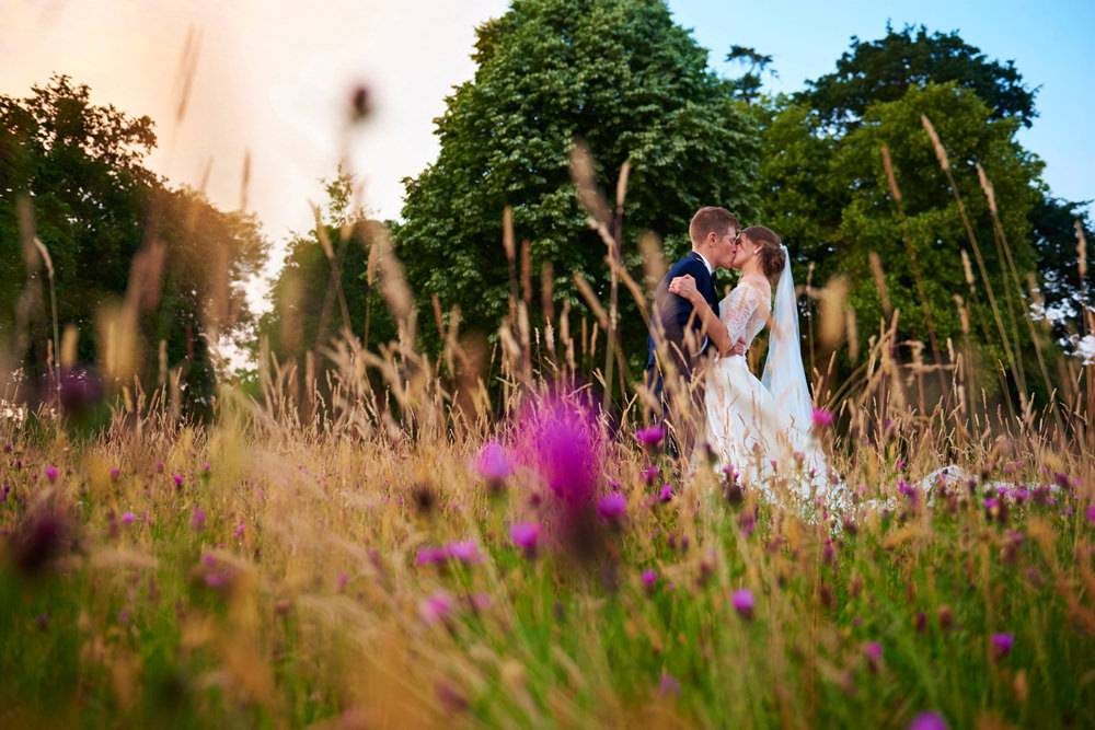 bride and groom in field of flowers kissing
