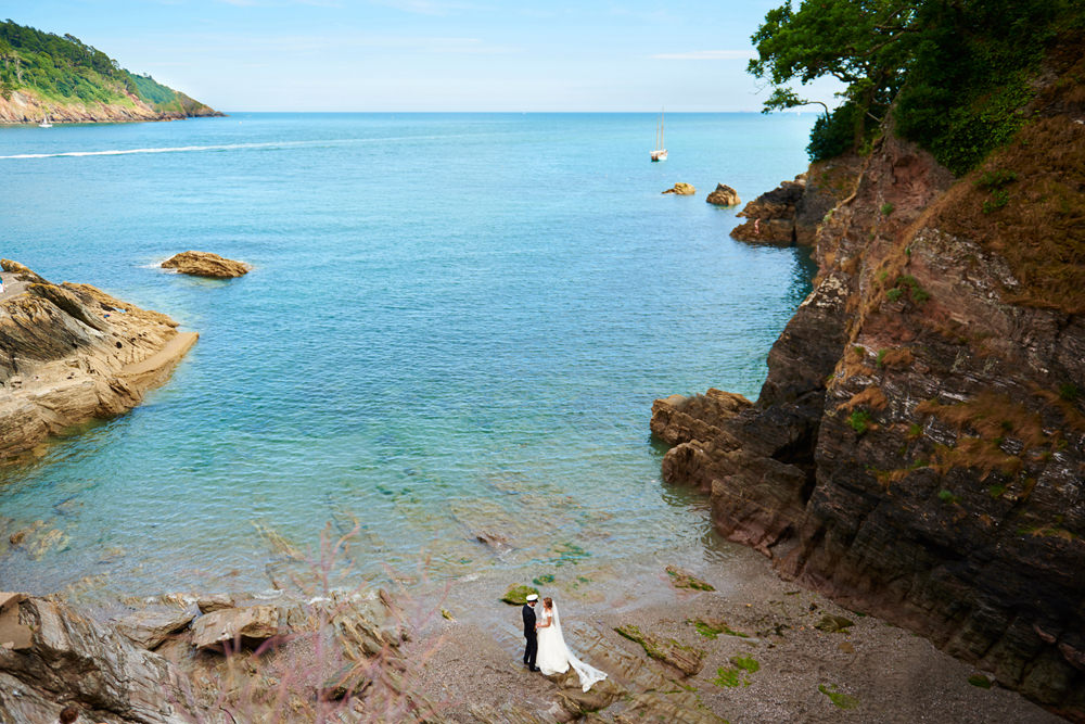 wide view from above of bride and groom on the beach with sea behind them- epic portrait