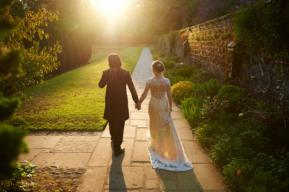 bride and groom walking with sun setting in gardens at dartington hall