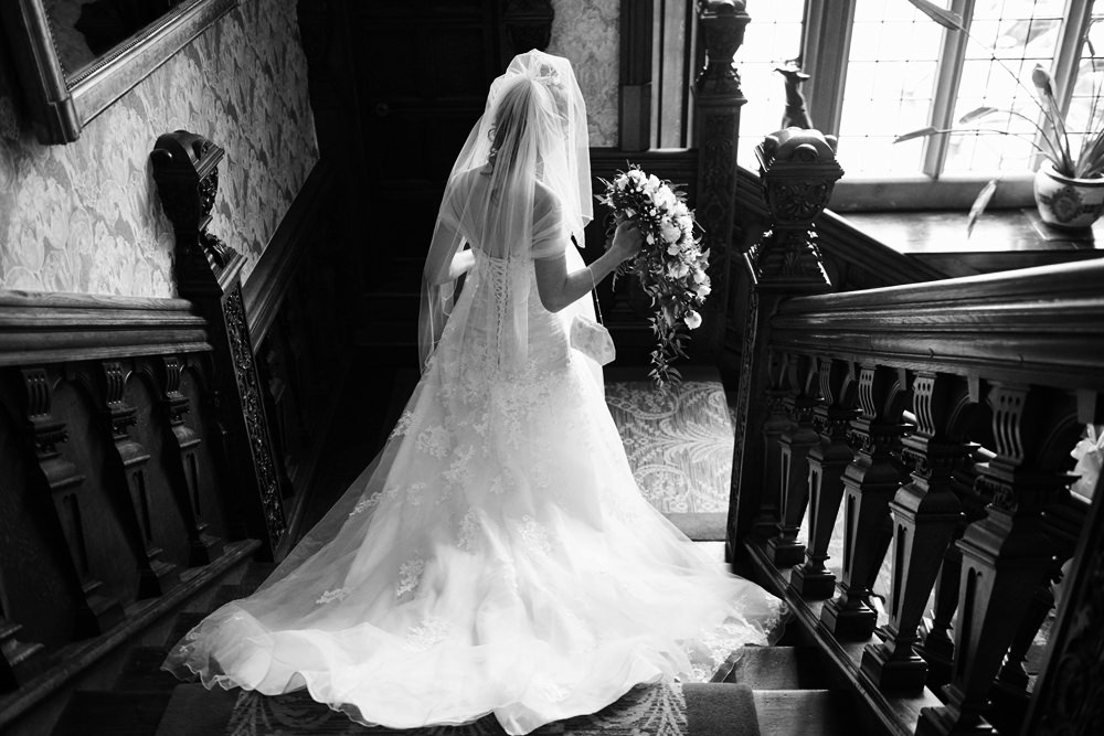 black and white shot of bride walking down the stairs to go and get married