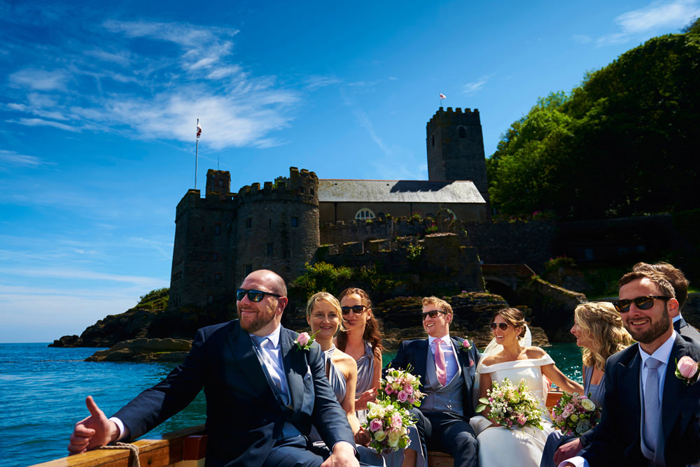 Dartmouth wedding - bride and groom in a boat with wedding guests and blue sky