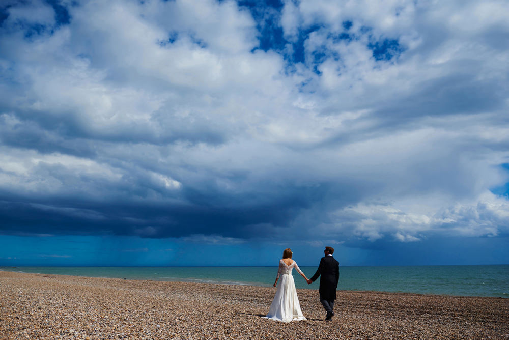 Branscombe wedding photographer- bride and groom walking on the beach