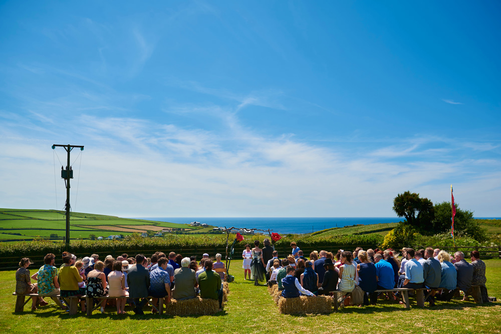 wide shot of outside humanist ceremony with sea in background