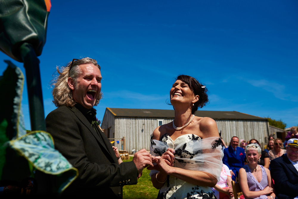 bride and groom exchanging rings during outside ceremony at Barn at South Milton in Devon