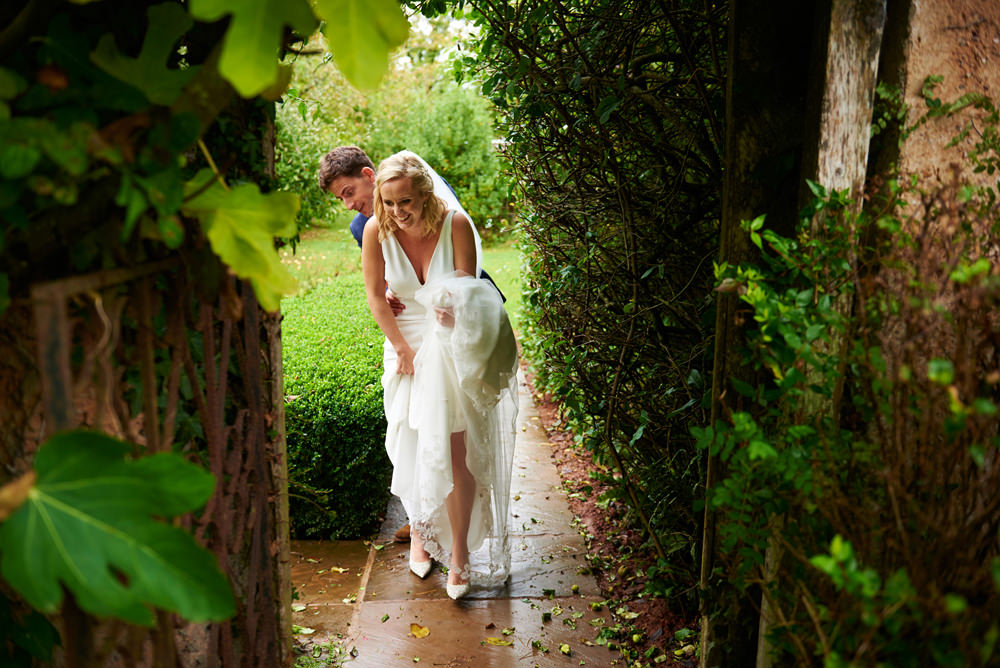 Hayne in Devon wedding photographer- bride and groom walking in the gardens through the arch